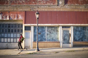 Man skateboarding down colorful street in vacated town.