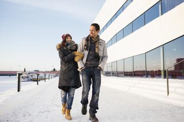 Sweden, Vasterbotten, Umea, Young couple walking along riverbank in winter
