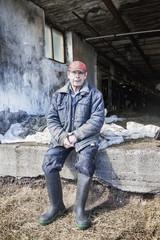 Sweden, Uppland, Grillby, Senior farmer sitting in front of barn
