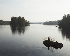 Sweden, Blekinge, Man crouching on rock on Lake Halen