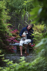 Sweden, Uppland, Man sitting with dog on bench in Japanese garden