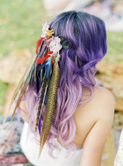 Sweden, Bride with flowers and feathers in purple hair at hippie wedding