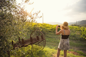 Woman taking picture with mobile phone while standing in vineyard