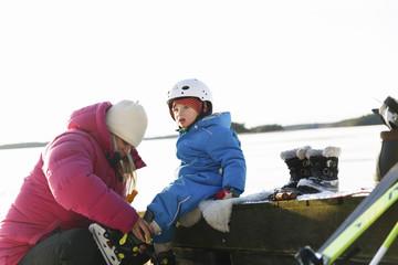 Sweden, Sodermanland, Jarna, Mother helping son (2-3) put ice skate