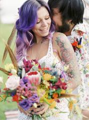 Sweden, Groom kissing bride at hippie wedding