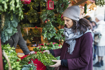 Sweden, Stockholm, Gamla Stan, Woman choosing christmas wreath at market