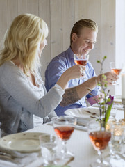 Sweden, Smiling man and woman raising wine glasses in celebratory toast