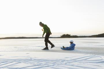 Sweden, Sodermanland, Jarna, Father with son (2-3) tobogganing