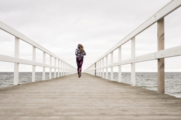 Sweden, Skane, Malmo, Rear view of young woman running on pier