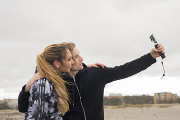 Sweden, Skane, Malmo, Young couple taking selfie on beach