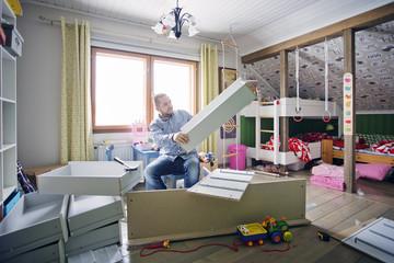 Finland, Man building cabinet in nursery