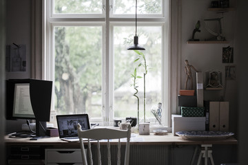 Sweden, Desk with laptop and computer monitor by window