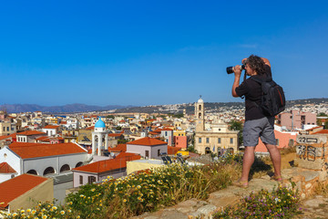 Photographer takes picture of medieval city with Orthodox cathedral Trimartiry from Schiavo Bastion in the sunny morning, Crete, Greece