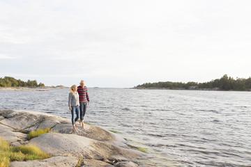 Sweden, Sodermanland, Vastra Stendorren, Couple walking barefoot along rocks by sea