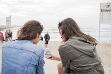 Israel, Tel Aviv, Rear view of women watching pictures on smart phone