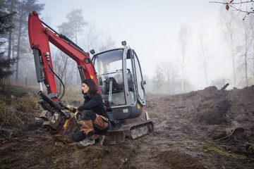 Sweden, Uppland, Nacka, Young female worker crouching by earth mover in fog