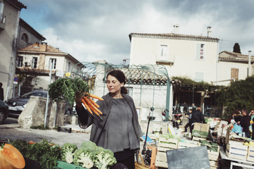 France, Languedoc-Roussillon, Sauve, Young tourist looking at carrot on market