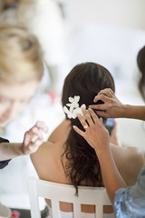 Sweden, Pinning flowers into young bride´s hairstyle