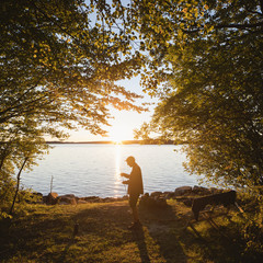 Sweden, Skane, Immeln, Mid adult man standing with fishing rod by river at sunset