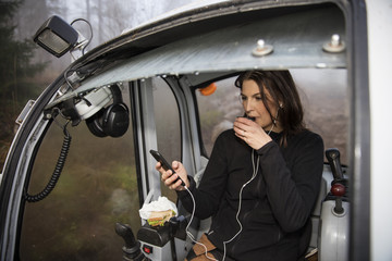Young woman using smart phone while drinking coffee