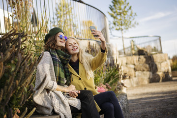 Sweden, Vasterbotten, Umea, Two young women taking selfie