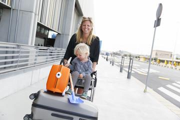 Spain, Gran Canaria, Maspalomas, Mother pushing son (2-3) on luggage cart