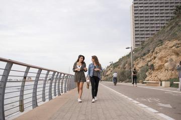 Israel, Tel Aviv, Two women walking along promenade