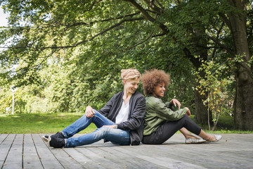 Sweden, Vastra Gotaland, Young smiling couple sitting on boardwalk in park