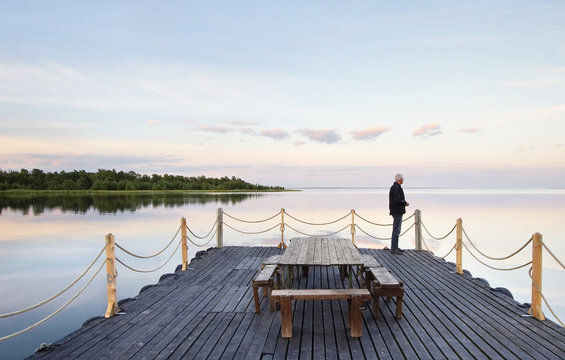 Senior man looking at sea while standing on wooden deck