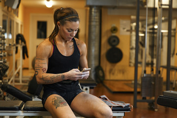 Young woman using mobile phone while sitting in gym