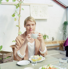 Woman holding cup of coffee and having breakfast on the table