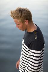 Sweden, Ostergotland, Teenage boy (16-17) standing by water