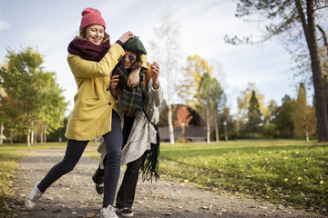 Sweden, Vasterbotten, Umea, Two young women grappling outdoors