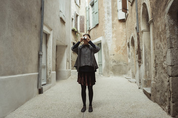 Young woman taking photo with camera in old town