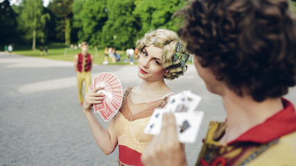Young circus performers holding playing cards in park