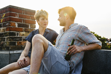 Germany, Berlin, Young couple sitting on rooftop holding beer
