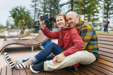 Australia, Queensland, Mid-adult couple taking selfie on bench in park