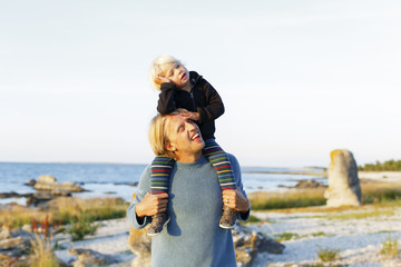 Sweden, Gotland, Farosund, Father carrying on shoulders little son (2-3)