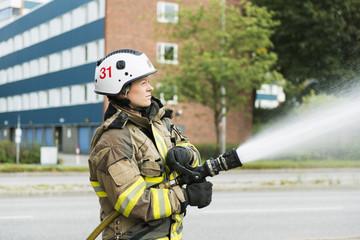 Firefighter using fire hose in street