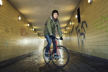 Portrait of man riding bicycle in tunnel