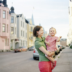 Finland, Uusimaa, Helsinki, Portrait of mother holding daughter (2-3) on street