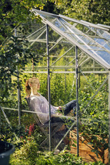 Finland, Heinola, Paijat-Hame, Woman relaxing in greenhouse
