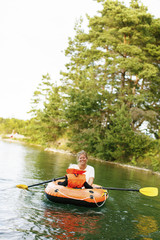 Sweden, Gotland, Farsund, Bastetrask, Woman with son (2-3) in inflatable raft on lake
