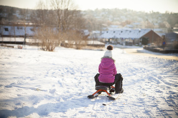 Sweden, Vastergotland, Lerum, Rear view of girl (8-9) sledding along snowy road with townscape in background