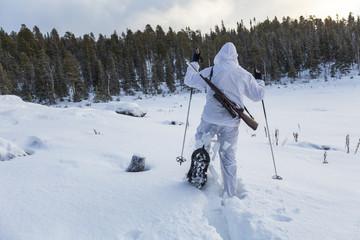 Sweden, Vasterbotten, Tarnaby, Goose hunter (16-17) snowshoeing in forest
