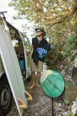 Australia, Queensland, Sunshine Coast, Noosa, Alexandria Bay, Young man standing by car and surfboards