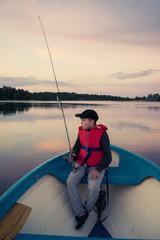 Boy fly fishing in lake during sunset