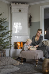 Sweden, Mother and daughter (6-7) sitting by fireplace opening Christmas presents