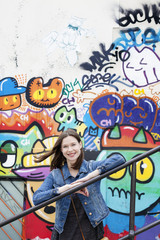 France, Ile-de-France, Paris, Young woman against wall with graffiti