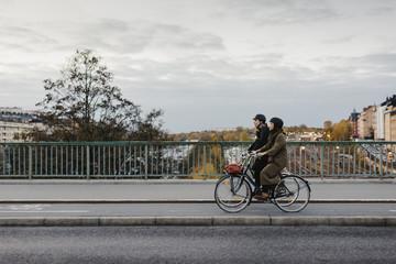 Sweden, Uppland, Stockholm, Vasatan, Sankt Eriksgatan, Man and woman cycling on city street
